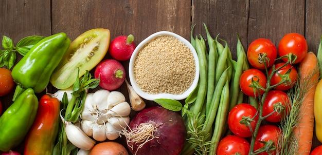 Couscous dans un bol et légumes frais sur vue de dessus en bois