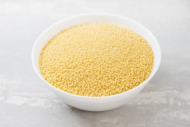 Couscous sec dans un bol blanc oin table en céramique