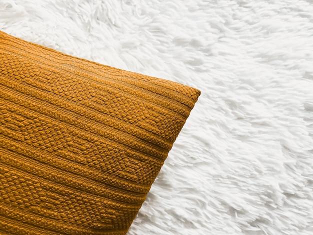 Coussin doré sur une couverture à carreaux moelleuse blanche comme vue de dessus de chambre à coucher à fond plat et...
