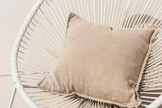 Coussin imprimé beige sur une chaise design d'intérieur minimal