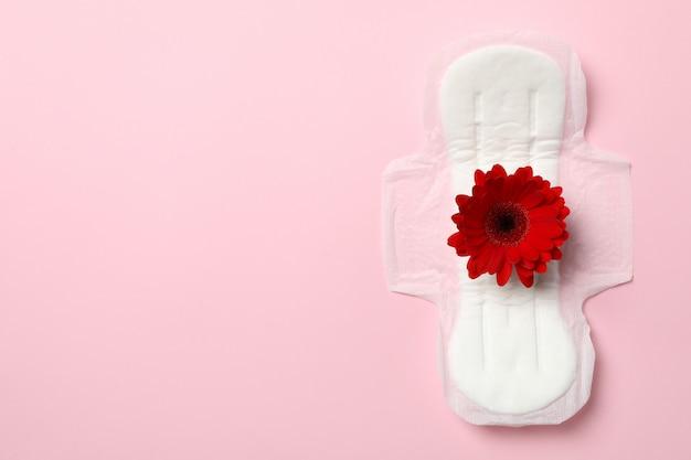 Coussin sanitaire avec gerbera sur surface rose