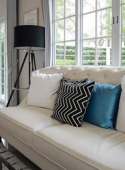 Coussins blancs et bleus sur un canapé en cuir blanc