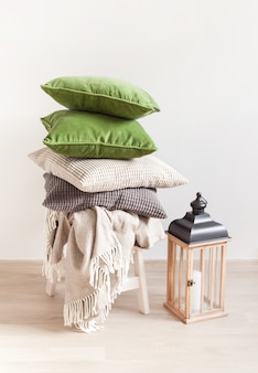 Coussins gris et verts, jet. maison confortable