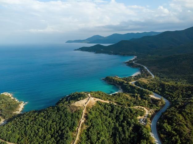 Coût de la mer égée de la grèce, route sinueuse, collines couvertes de verdure luxuriante