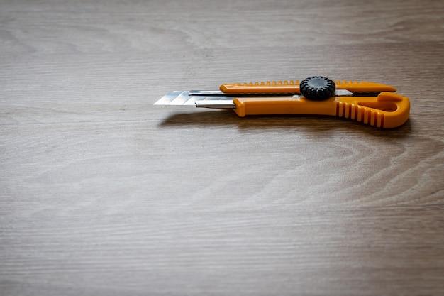Couteau boîte jaune sur fond de bois, gros plan avec mise au point sélective et espace de copie.