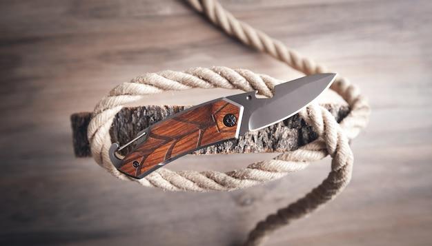 Couteau brun, corde et tranche d'arbre sur table en bois.