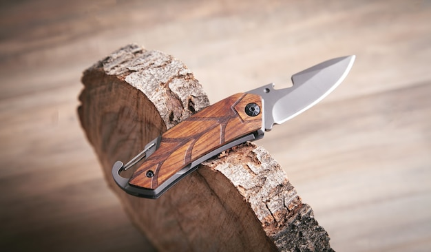 Couteau brun et tranche d'arbre sur fond de bois.