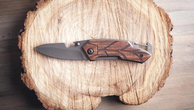 Couteau brun et tranche d'arbre sur table en bois.