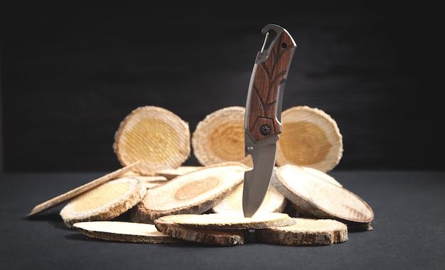 Couteau brun et tranches d'un arbre sur fond noir.