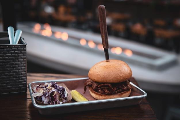 Couteau coincé dans un burger sur un plateau métallique sur le toit