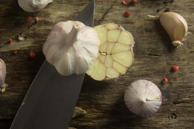 Couteau coupe l'ail sur une planche de cuisine rustique