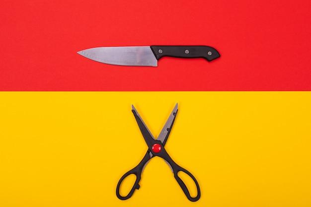 Couteau de cuisine et des ciseaux se trouvent isolé un jaune-rouge