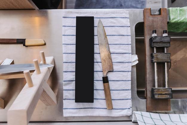 Couteau de cuisine japonais terne et rustique en attente d'affûtage sur du tissu blanc à rayures bleues.