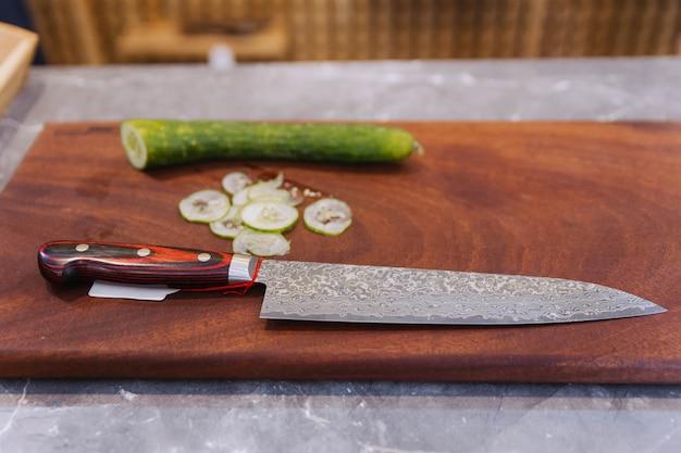 Couteau de cuisine japonais tranchant avec des tranches de courgettes ultra fines sur une planche à découper en bois.