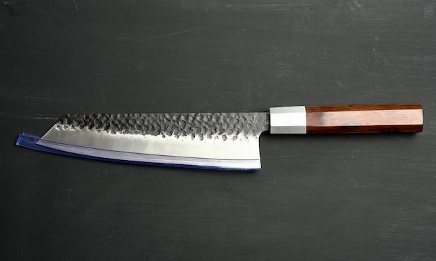 Couteau de cuisine en métal avec manche en bois sur fond noir, gros plan