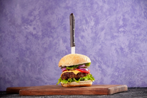 Couteau dans un délicieux sandwich à la viande sur une planche à découper en bois sur une surface de glace isolée avec espace libre