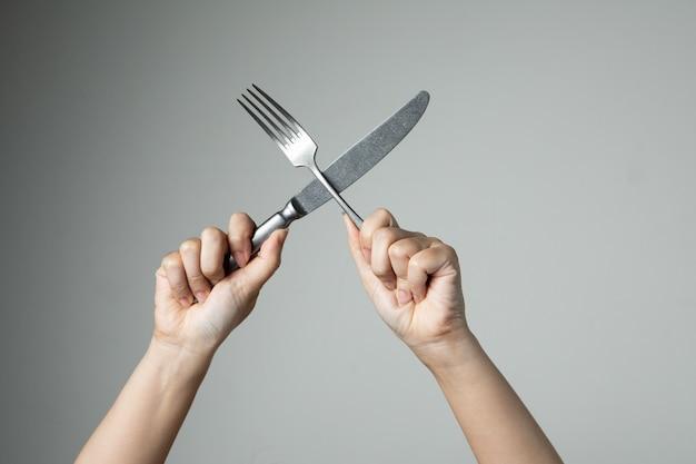 Couteau et une fourchette avec la main sur la cuisine ustensile fond gris pour la cuisine