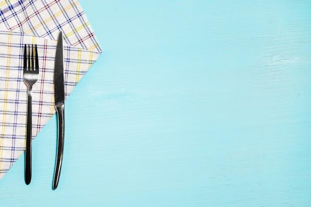 Couteau et une fourchette sur une serviette en cage sur une table en bois bleue