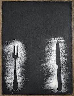 Couteau et fourchette silhouettes de farine sur schiste noir