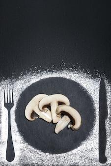 Couteau, fourchette et silhouettes de plaque avec de la farine sur le schiste noir.