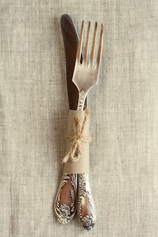 Couteau et fourchette vintage sur la nappe sur une surface claire
