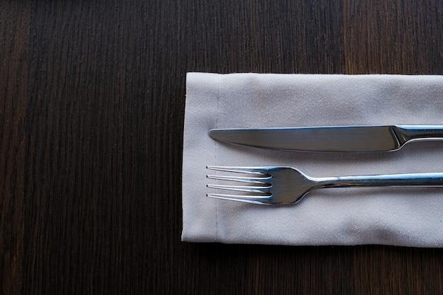 Un couteau en métal et une fourchette sur une serviette sur la table. nettoyer les couverts pour la nourriture. réglage de la table.