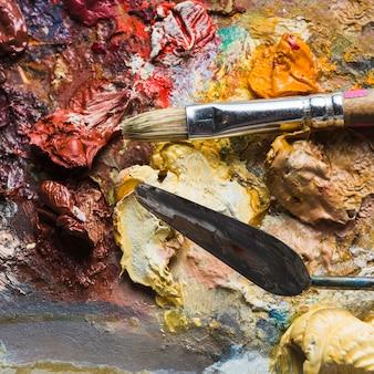 Couteau à palette mélangeant la peinture près de la brosse