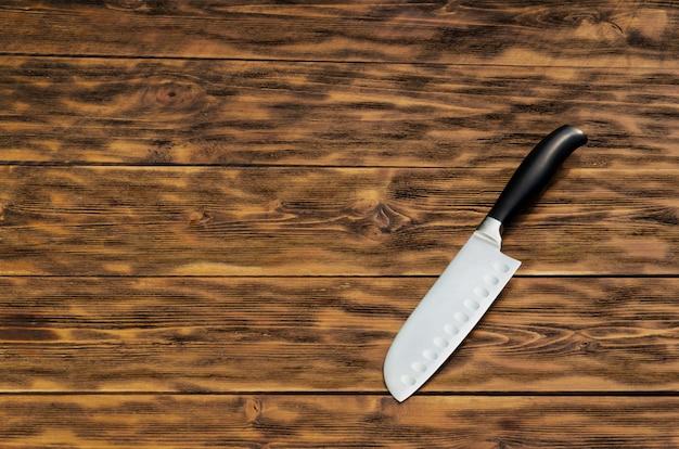 Le couteau repose sur la vieille surface en bois
