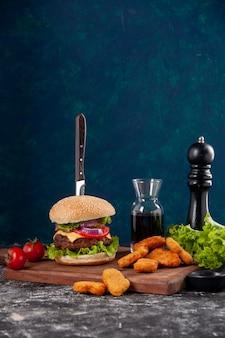 Couteau en sandwich à la viande et nuggets de poulet tomates avec tige de poivre sur planche de bois sauce ketchup sur surface bleu foncé