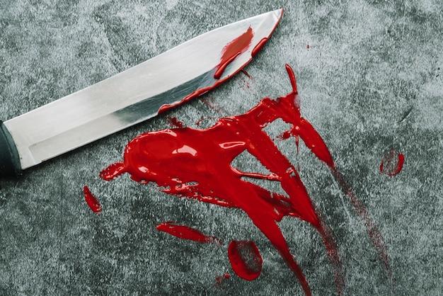 Couteau et sang artificiel sur la surface de la pierre