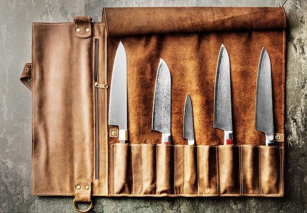 Les couteaux japonais de différentes tailles en acier damas sont dans un étui en cuir. concept d'entreprise de croissance de carrière