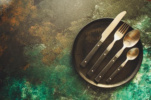 Coutellerie rustique, utilisée pour manger ou servir (fourchette, couteau, cuillère, assiette).
