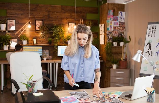 Couturier féminin dans le bureau créatif vérifiant ses idées. assistant en arrière-plan.