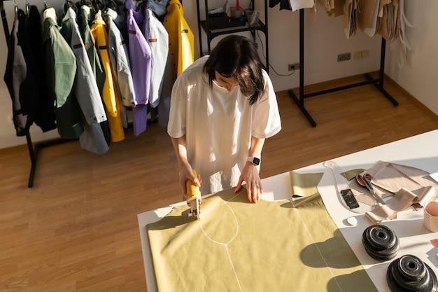 Le couturier de processus de couture et de coupe travaille avec des modèles sur le tissu pour la collection dans le studio d'atelier