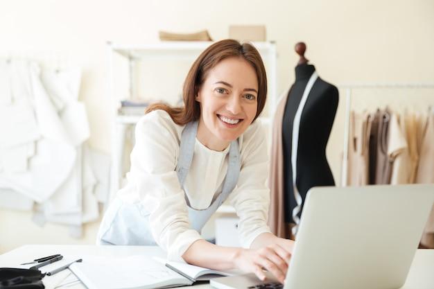 Couturière à l'aide d'un ordinateur portable pour le travail