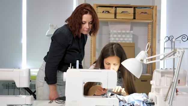 La couturière apprend à un nouvel employé à travailler en atelier. cours de coupe et couture. le professeur de couturière contrôle comment les élèves cousent sur une machine à coudre dans un atelier. notion de stage. période de probation.
