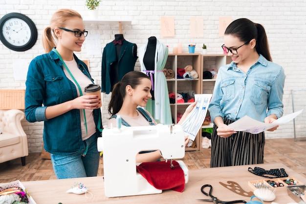 Couturière et assistantes regardant un croquis