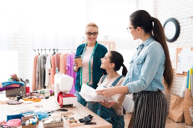 Couturière au travail et assistantes ramassant le matériel