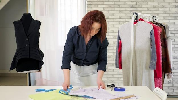 Couturière au travail dans son atelier de couture. une femme sur mesure mesure le tissu avec du ruban adhésif sur la table pour créer un motif pour les futurs vêtements sur le lieu de travail. affaires sur la couture individuelle.