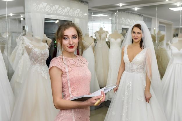 Couturière avec bloc-notes dans le salon de mariage et la mariée