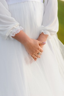Couturière boutonnant la jolie robe de mariée