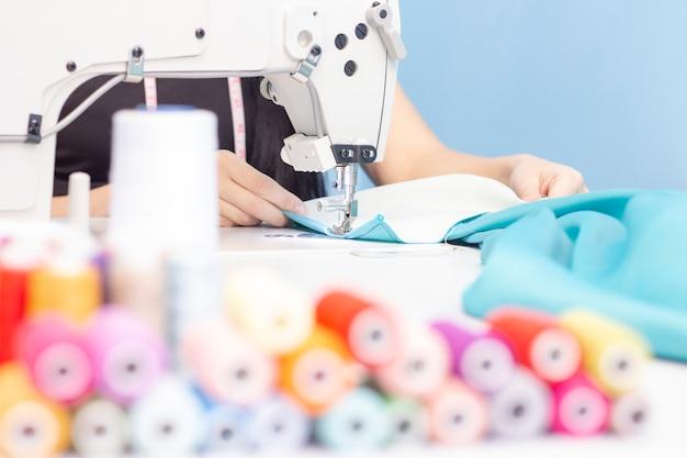 Couturière à coudre sur un gros plan de machine à coudre. un ensemble d'articles pour la couture: fils, aiguilles, épingles, ciseaux, ruban à mesurer, etc.