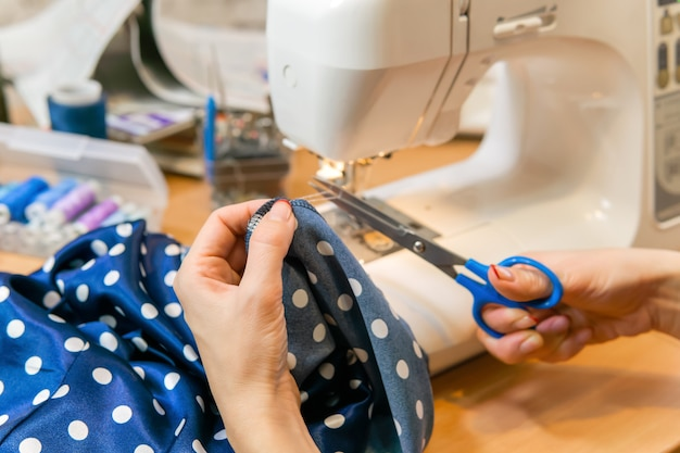 La couturière coupe le fil lorsqu'elle a fini de coudre le bord du tissu avec une machine à coudre