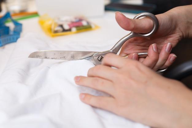La couturière coupe des paires de ciseaux en tissu