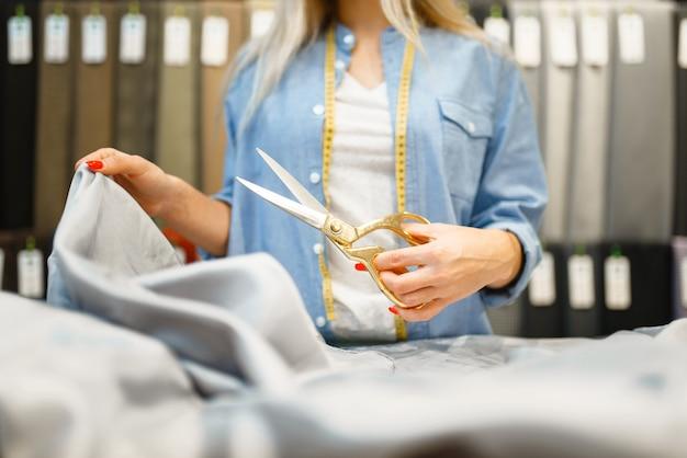 La couturière coupe le tissu avec des ciseaux en magasin