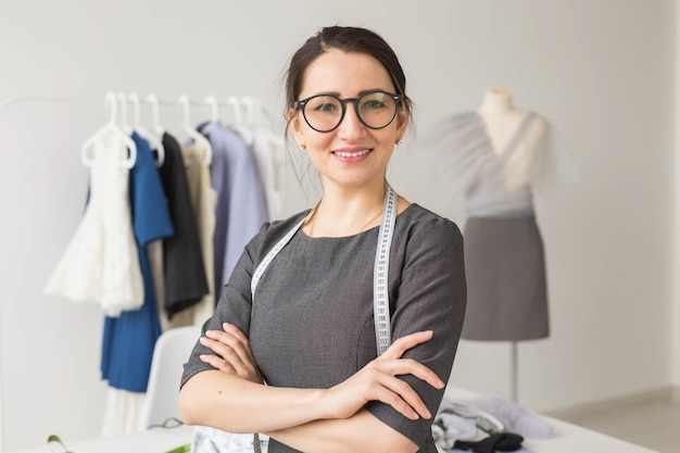 Couturière, créateur de mode et concept de tailleur - jeune couturière femme sur étendoir avec