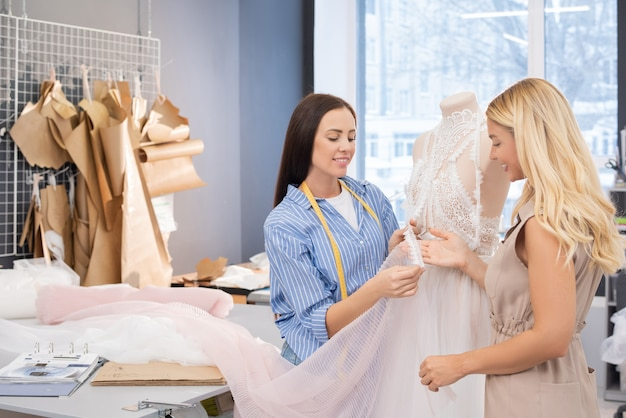 Couturière démontrant la robe de mariée au client