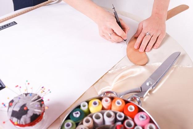 La couturière dessine un modèle pour le futur produit.