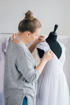 Couturière fait une robe ajustée sur le mannequin