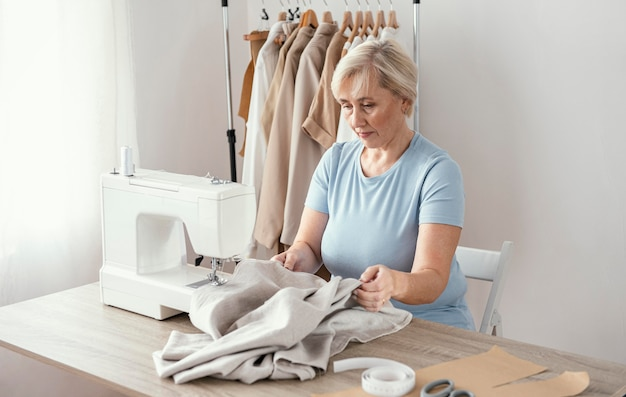 Couturière féminine dans le studio à l'aide de machine à coudre